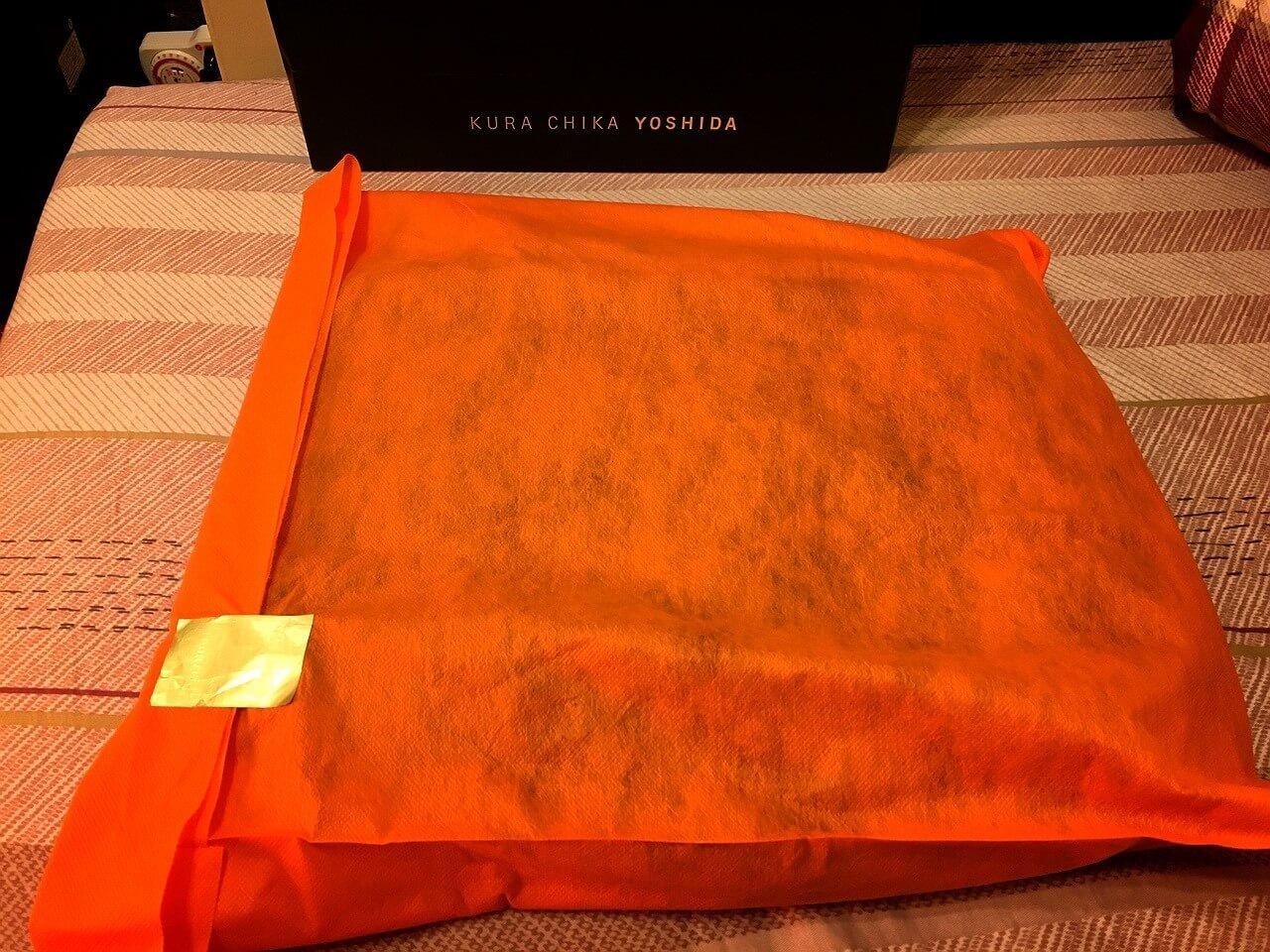 拿出提袋後,用一層橘色的不織布包覆著