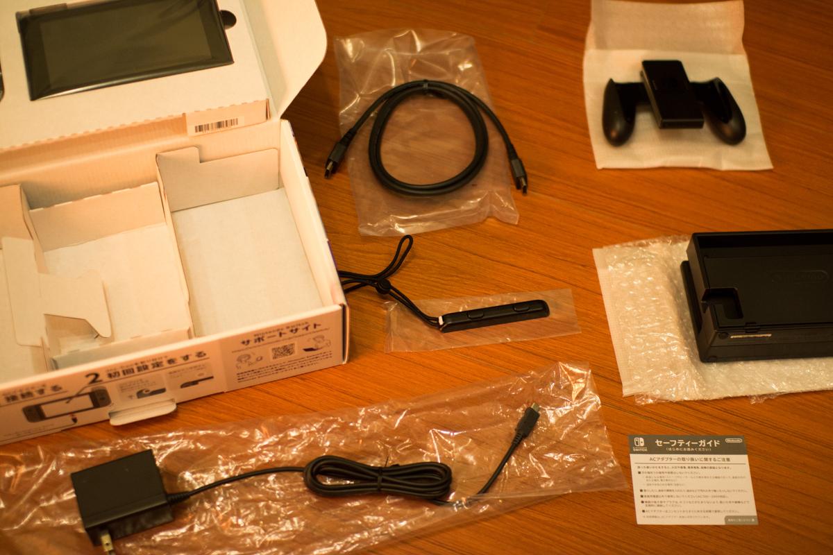盒裝下層分別有 AC變壓器、底座、Joy-Con 握把、Joy-Con 腕帶、HDMI 連接線、日文說明書